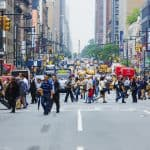 Commuters crossing busy 8th Avenue in New York City, USA in afternoon. Vast number of people and vehicles hit the streets and avenues of Manhattan every day.